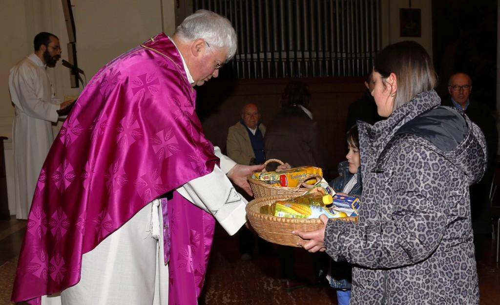I doni per i bisognosi portati dalla Caritas all'Offertorio
