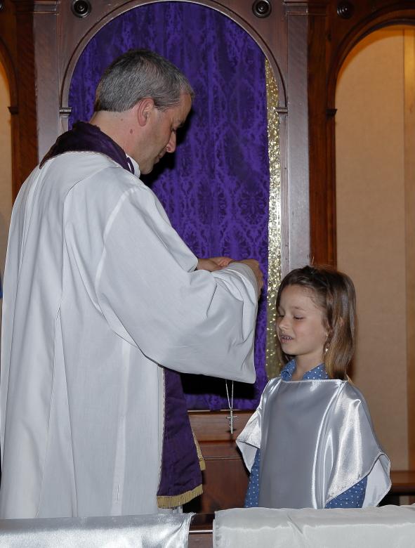 Una bambina riceve la croce che dovrà portare il giorno della Comunione