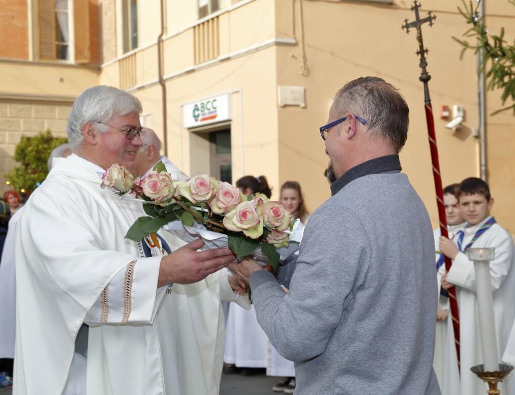 """Don Pietro consegna il mazzo di rose al tecnico che lo porterà alla statua della """"Patrona Municipii"""""""