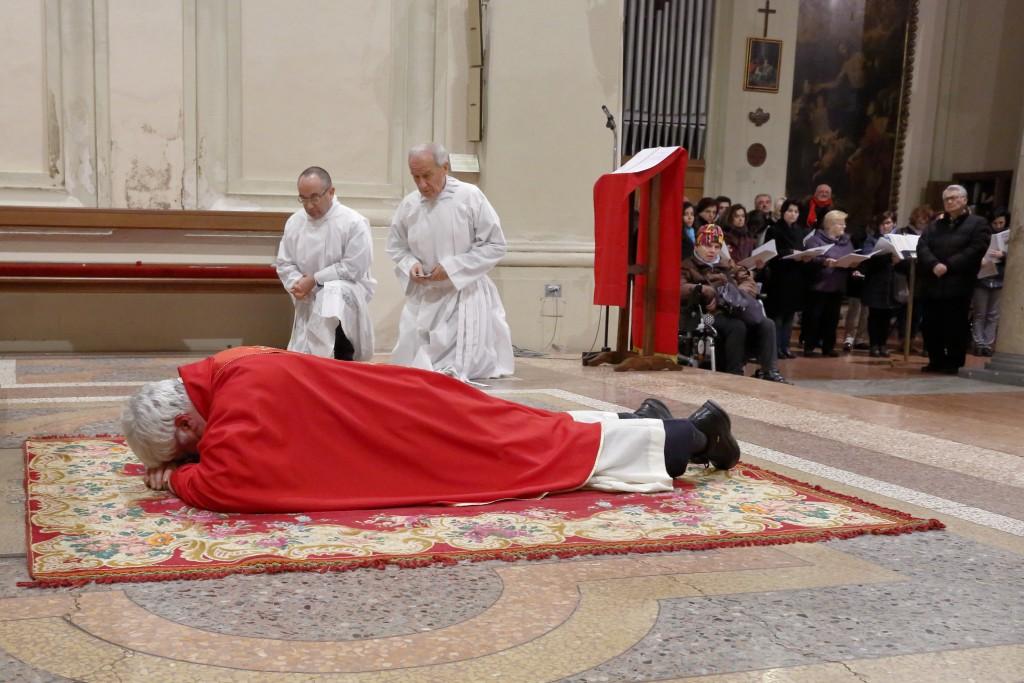 Il celebrante, prostrato, prega all'inizio della celebrazione