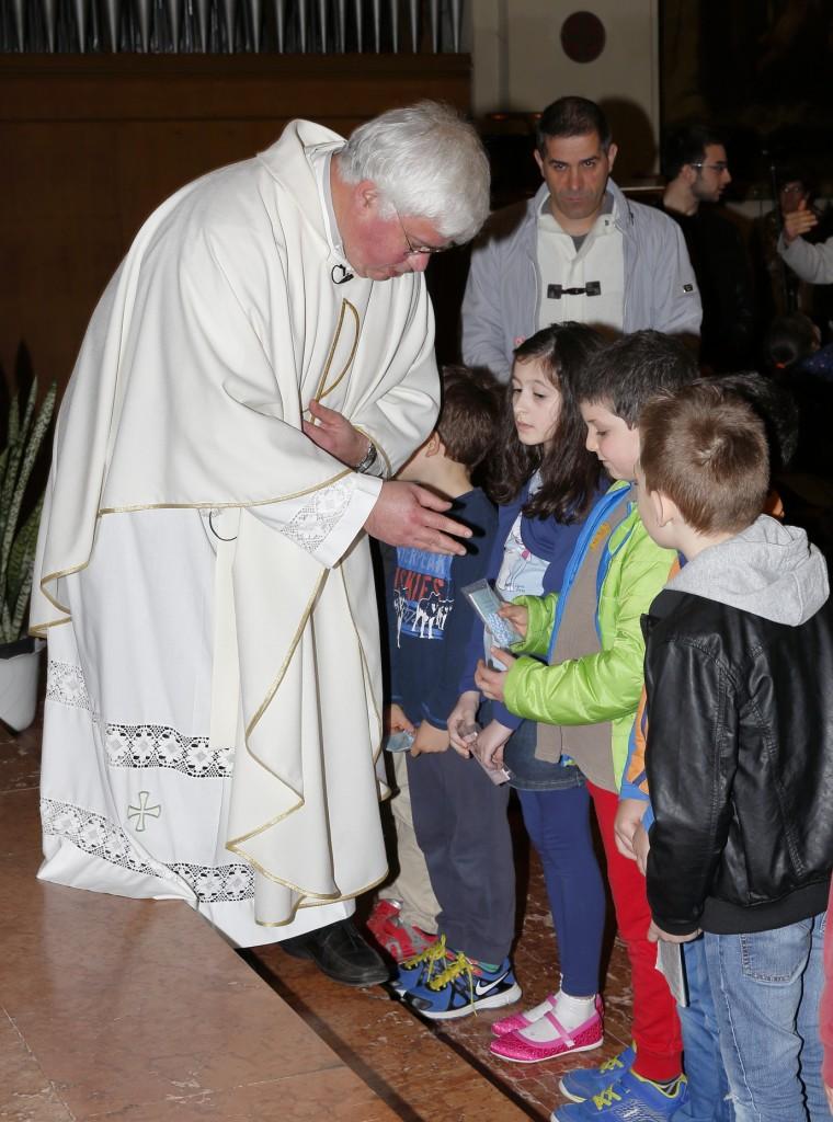 Alcuni bambini ricevono dalle mani di Don Pietro la corona del Rosario