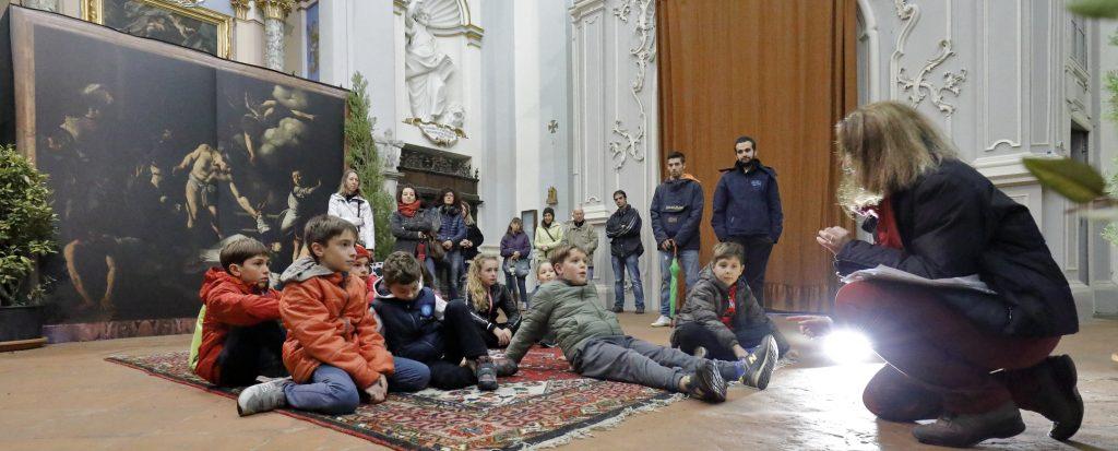I ragazzi del quarto anno di catechismo ascoltano le spiegazioni sui quadri del Caravaggio accompagnati da catechisti e genitori
